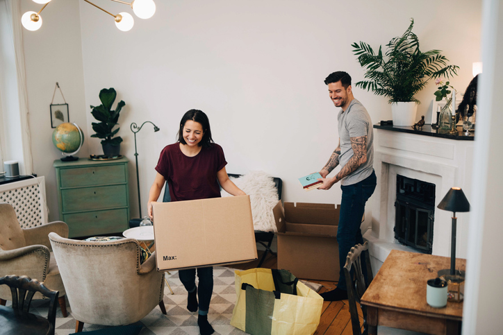 http://Happy%20Couple%20Unpacking%20Boxes%20In%20Living%20Room%20At%20New%20Home